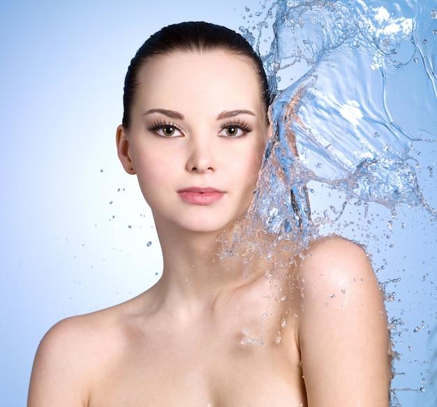 体色の空間に水しぶきを持つ美しい若い女性
