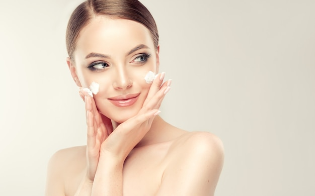 Beautiful, young woman with spots of cosmetic cream on the on the well groomed skin