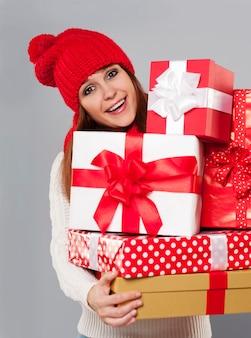 Bella giovane donna con una pila di regali di natale