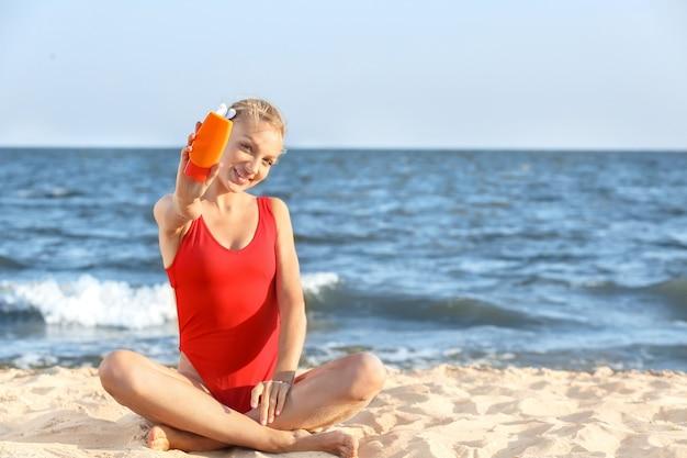 海のビーチで日焼け止めクリームを持つ美しい若い女性