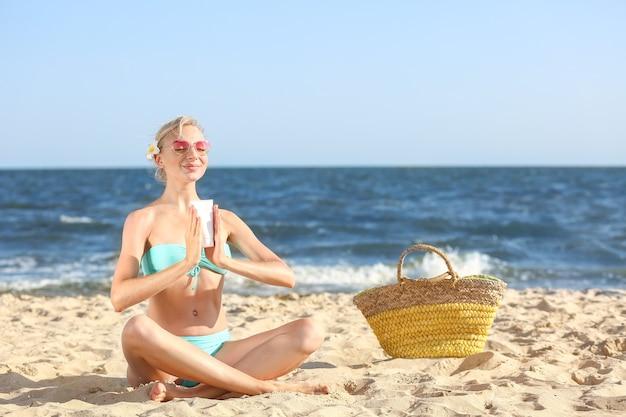 Красивая молодая женщина с солнцезащитным кремом на морском пляже
