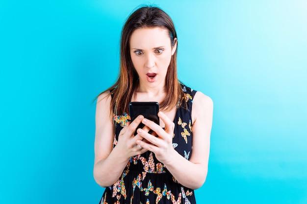 Красивая молодая женщина с удивленным лицом, глядя на смартфон на синем фоне с copyspace