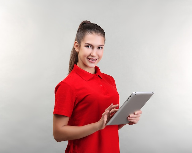 가벼운 표면에 태블릿 컴퓨터와 아름 다운 젊은 여자