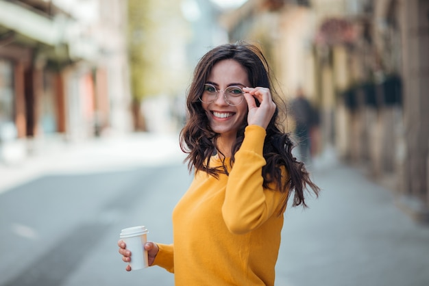 Beautiful young woman with takeaway coffee walking in the city on a sunny day.