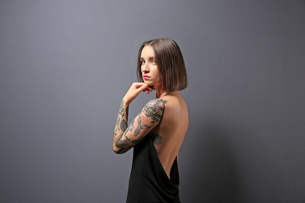 灰色のポーズの入れ墨を持つ美しい若い女性