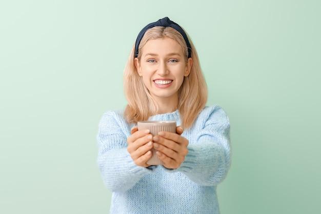 Красивая молодая женщина с чаем на цветном фоне
