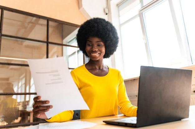 사무실에서 일하는 아프리카 머리를 한 아름다운 젊은 여성