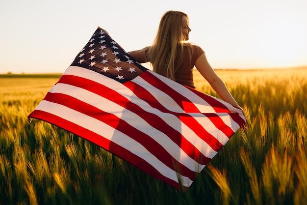 Красивая молодая женщина с американским флагом в пшеничном поле на закате