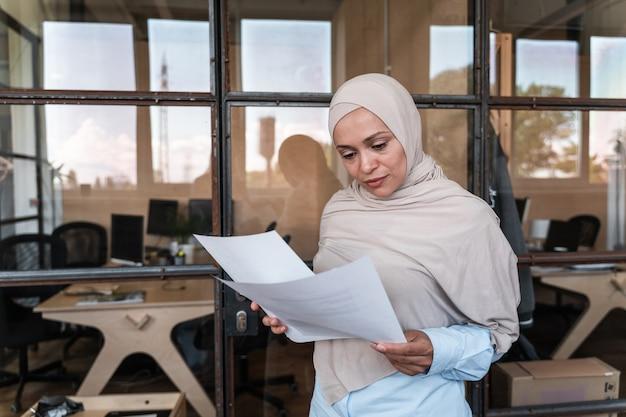 사무실에서 일하는 히잡을 쓴 아름다운 젊은 여성 프리미엄 사진