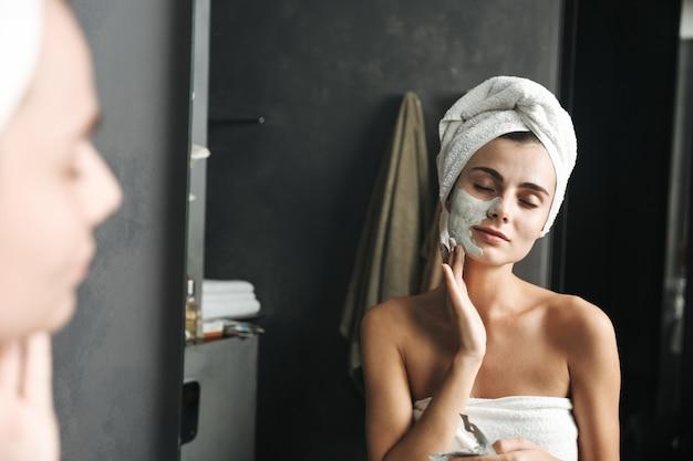 수건으로 아름 다운 젊은 여자 화장실에서 얼굴 마스크를 적용하는 그녀의 머리를 감싸