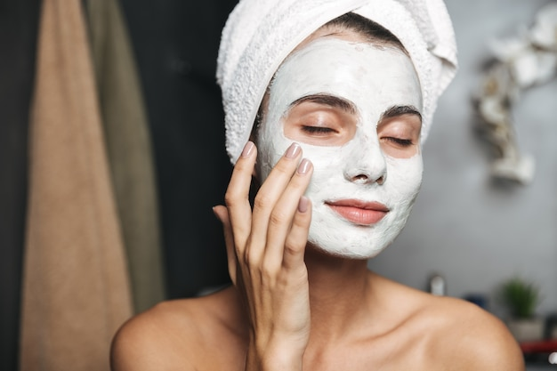 Beautiful young woman with towel wrapped around her head applying face mask at the bathroom