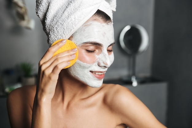 Beautiful young woman with towel wrapped around her head removing face mask with a sponge at the bathroom