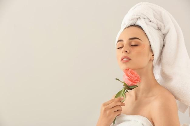 目の下のパッチとベージュの花を持つ美しい若い女性