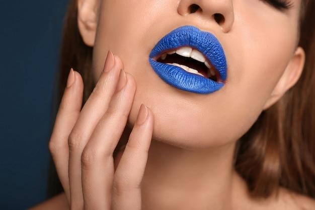 色の表面、クローズアップに珍しい口紅を持つ美しい若い女性