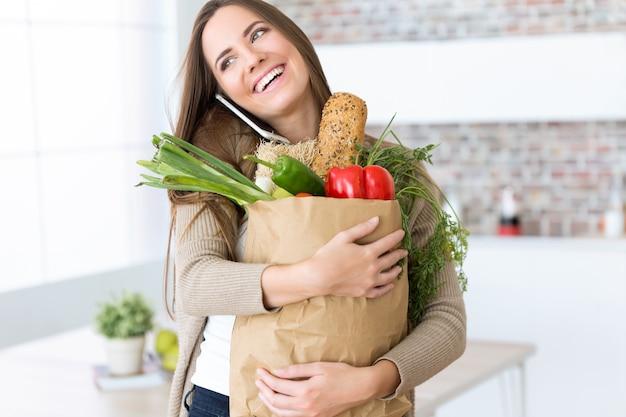 Красивая молодая женщина с овощами в продуктовой сумке у себя дома.