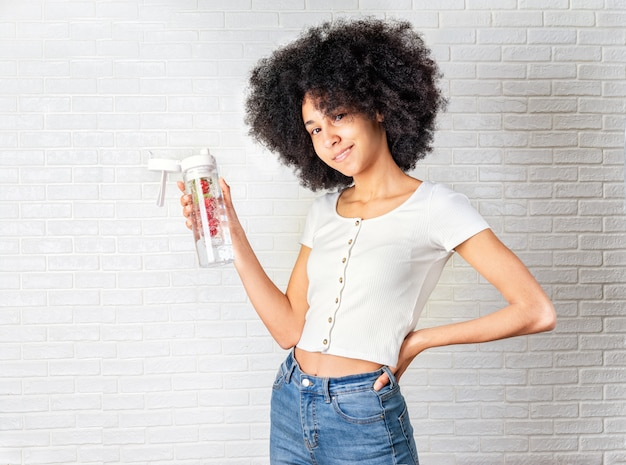 Beautiful young woman with water of infused water