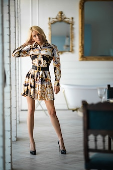 Красивая молодая женщина с волнистыми светлыми волосами в новом стильном платье и туфлях позирует в роскошной квартире