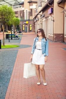 흰색 가방 거리에 쇼핑 데 아름 다운 젊은 여자