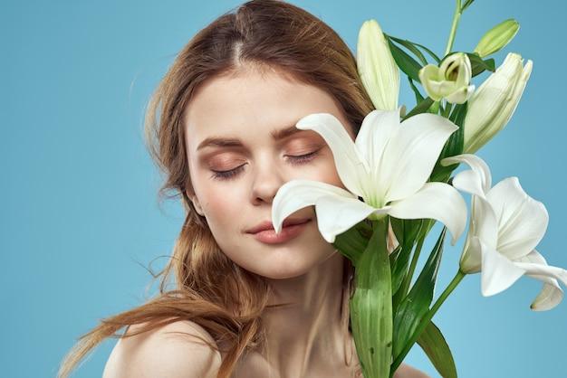 Красивая молодая женщина с цветком белой лилии позирует синий