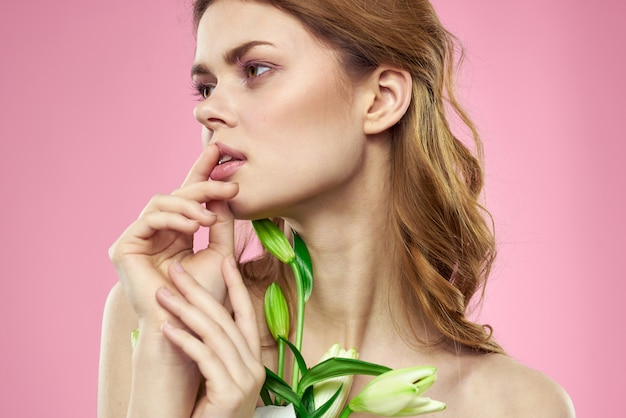Красивая молодая женщина с цветком белой лилии позирует в студии на розовом, романтичном нежном изображении