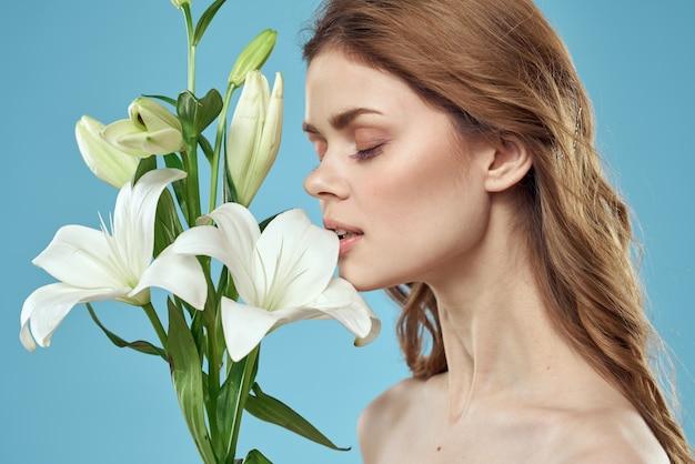Красивая молодая женщина с белой лилией позирует