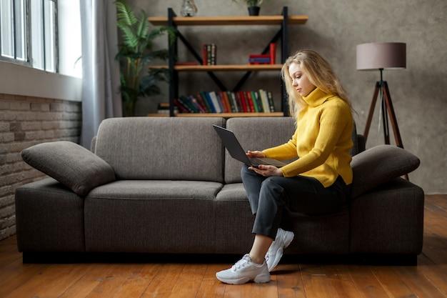 Красивая молодая женщина, работающая из дома на ноутбуке, сидя на диване в гостиной. фото высокого качества