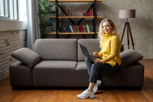 Красивая молодая женщина, работающая дома на ноутбуке, сидя на диване в гостиной