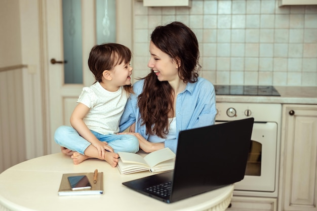 Beautiful young woman working in a home office sitting at a table in the kitchen with a laptop. next to her is her little baby daughter. they are smiling happily