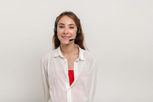Красивая молодая женщина, работающая в call-центре с наушниками и улыбающаяся