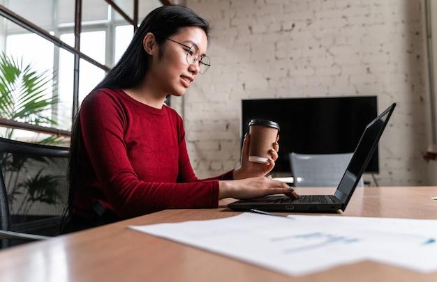 노트북에 사무실에서 일하는 아름 다운 젊은 여자.