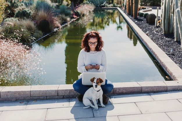 Beautiful young woman working on laptop. with her dog besides. outdoors. sunny