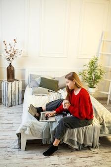 Красивая молодая женщина, работающая на ноутбуке, сидя на кровати у себя дома, она пьет кофе и улыбается. работа из дома во время карантина. девушка в свитере и джинсах дома на кровати