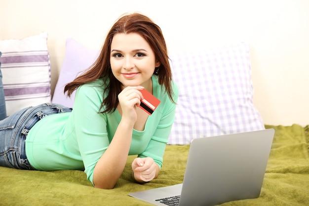 방에 노트북에서 일하는 아름 다운 젊은 여자