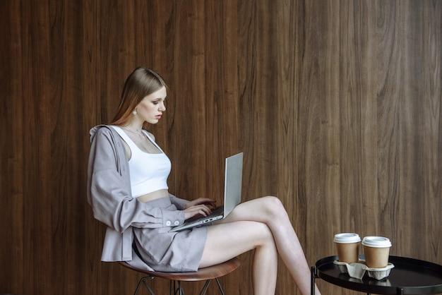 앉아있는 동안 인터넷을 사용하여 노트북에서 작업하는 아름다운 젊은 여성