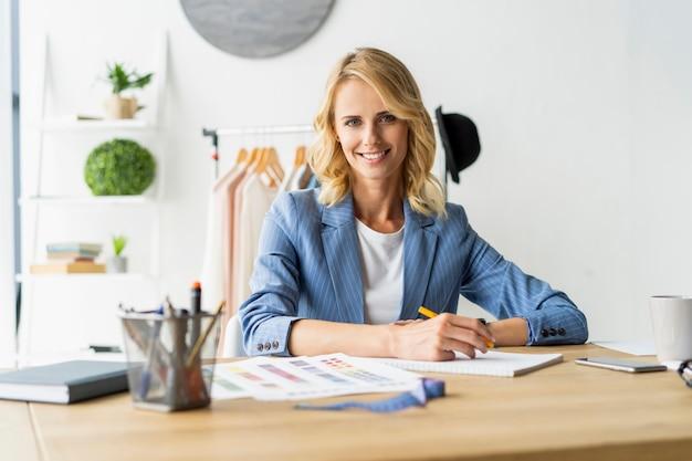 선반에 매달려 옷 근처에 그녀의 스튜디오에서 스케치 작업 아름다운 젊은 여자