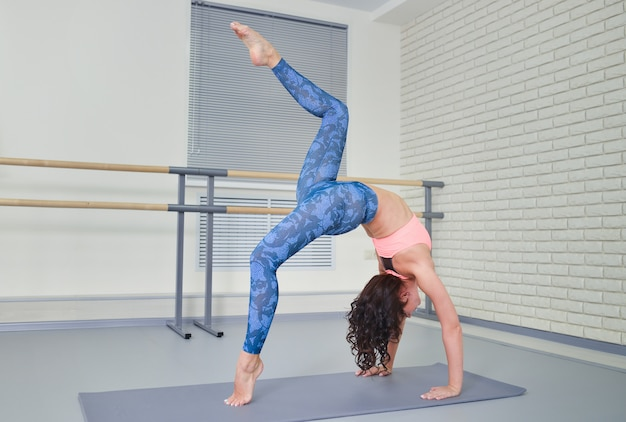 Beautiful young woman working out in fitness class, doing yoga exercise on mat, stretching, standing in bridge pose, full length