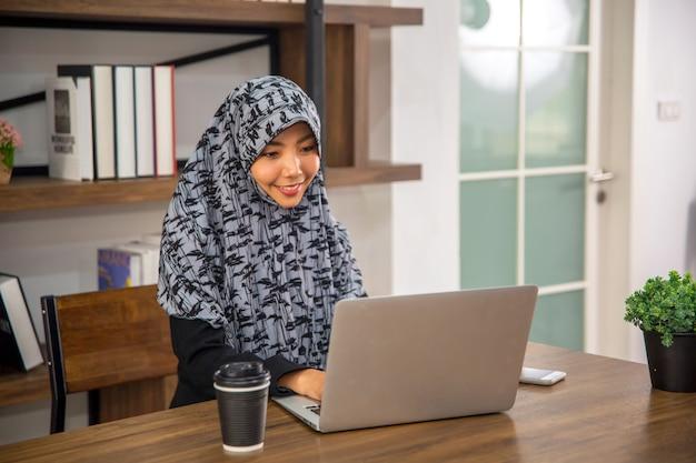 집중하고 웃고 있는 컴퓨터 노트북을 사용하여 일하는 아름다운 젊은 여성