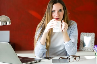 Beautiful young woman working with laptop in her office.
