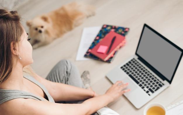 Красивая молодая женщина работает из дома. собака лежит рядом с ней.
