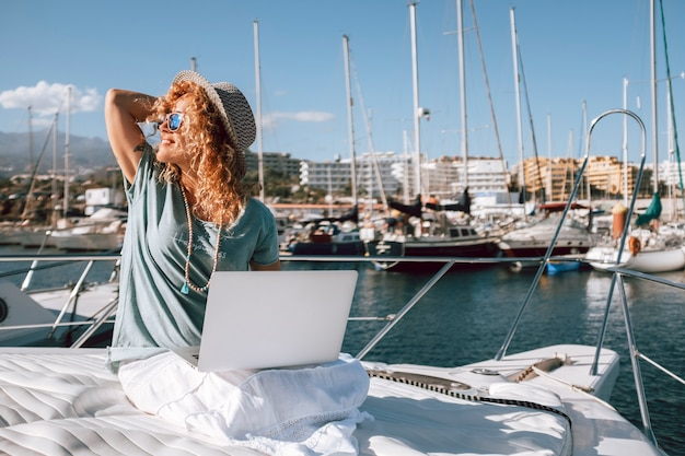 Beautiful young woman works with laptop computer in alternative office boat at the dock