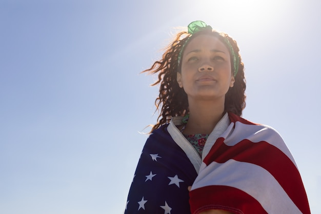 Beautiful young woman wrapped in american flag on beach in the sunshine