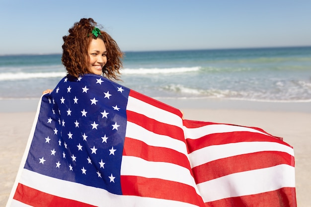 Beautiful young woman wrapped in american flag looking at camera on beach in the sunshine