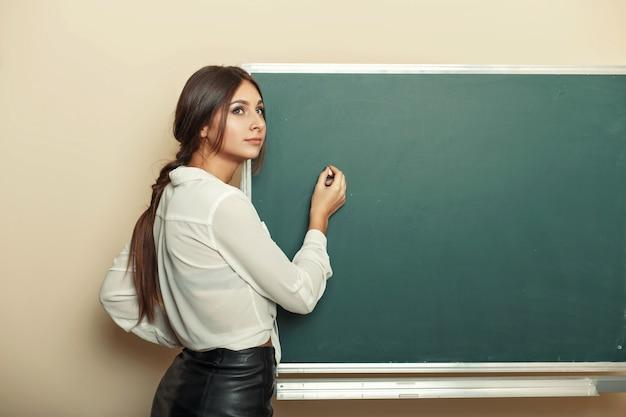 美しい若い女性が黒板にチョークを書く