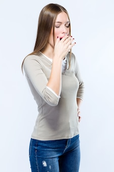 Beautiful young woman yawning over white background.