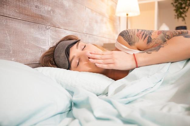 寝室で眠りに落ちながらあくびをする美しい若い女性。