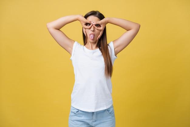 Bella giovane donna su sfondo giallo faccia felice sorridente facendo ok o segno di vetro con la mano sull'occhio guardando attraverso le dita.