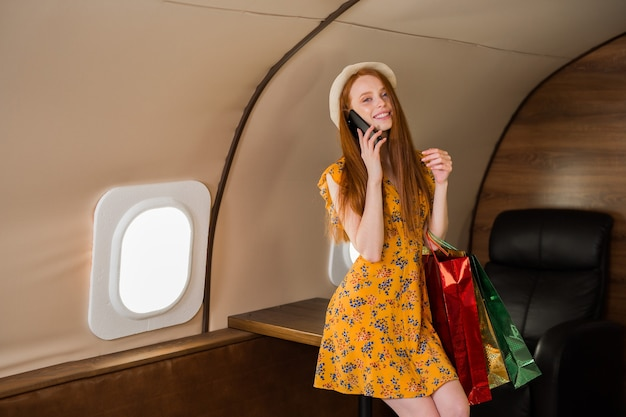 Beautiful young woman in yellow dress in a private jet with packages