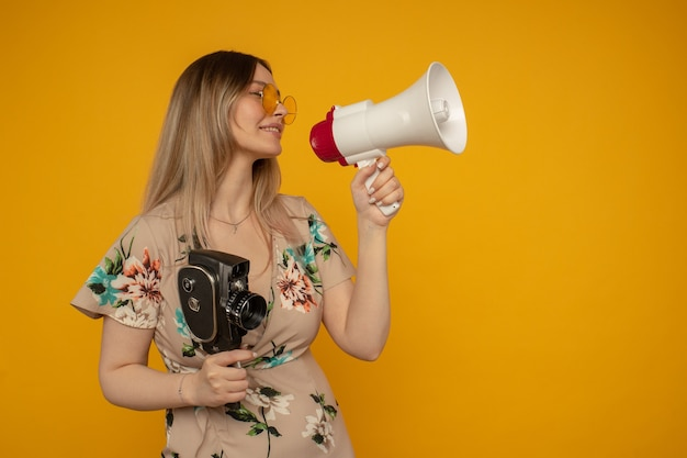 Beautiful young woman in yellow glasses posing with film camera and megaphone