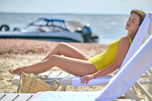 A beautiful young woman in a yellow swimming suit sunbathing