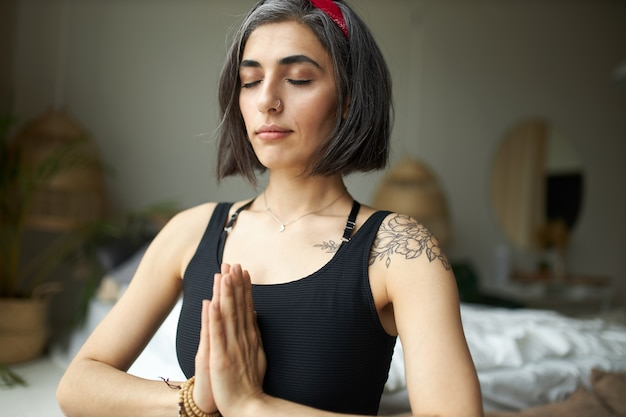Beautiful young womanwith grayish hair, tattoo on shoulder and nose ring pressing hands together in namaste at heart chakra